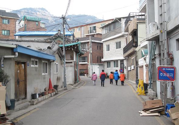 동네에 사는 아이들이 다함께 노래를 부르며 걷고 있다.