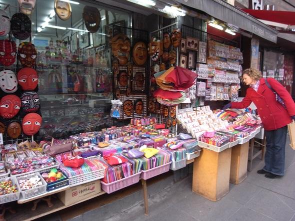 인사동 거리 길 상점에 전시된 탈, 자수 공예품 등을 구경하는 관광객.