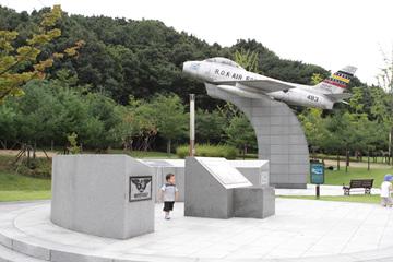 보라매공원의 드넓은 잔디광장(좌)과 과거 공군사관학교가 있었음을 짐작게 하는 전투기모형(우).