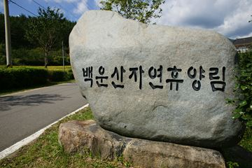 백운산자연휴양림의 표지석(좌)과 휴양림 내 물레방아의 모습(우).
